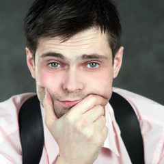 Thoughtful young man in pink shirt on gray background