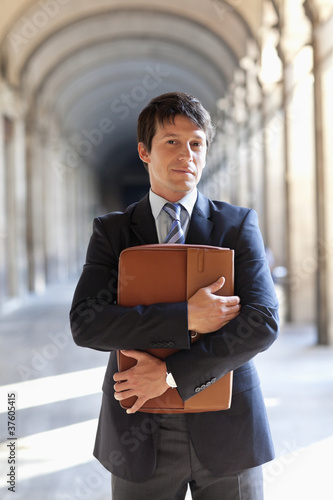 Businessman standing outdoors holding briefcase
