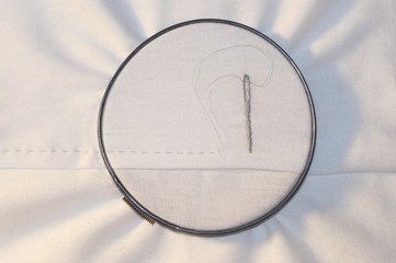 Embroidery hoop with running stitch and needle on cotton fabric