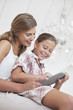 Mother and daughter using digital tablet together