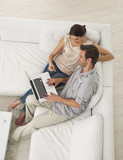 Couple sitting on sofa shopping online with credit card