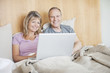 Couple sitting in bed using laptop together
