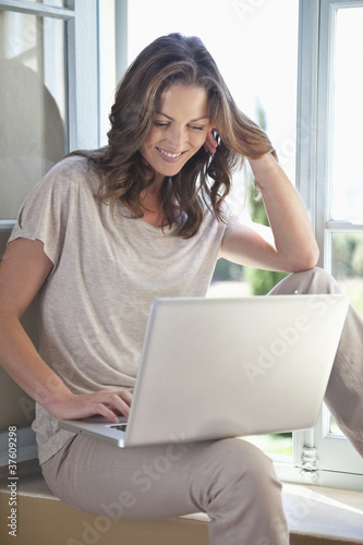Woman sitting near window using laptop