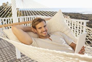 Man laying in hammock using digital tablet