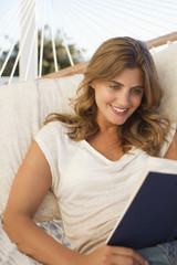 Woman laying in hammock reading book