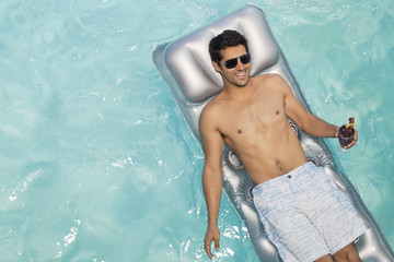 Man floating in swimming pool drinking cocktail