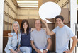 """Friends at back of moving van, one holding a comment bubble"""