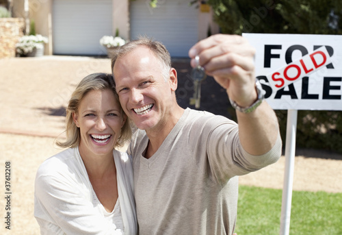 Proud couple holding keys to new home
