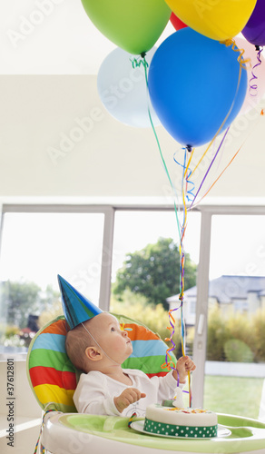 Baby with birthday cake holding balloons