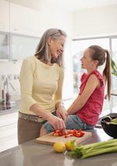 Grandmother and granddaughter preparing food together