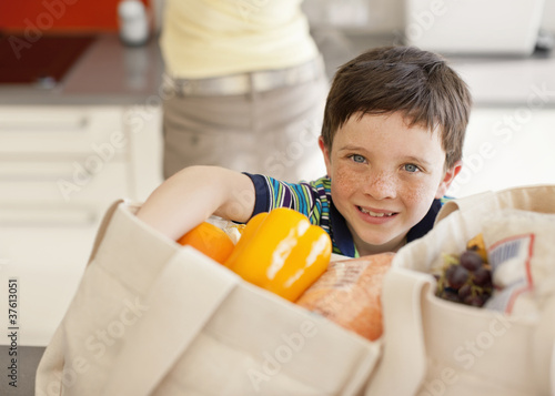 Boy unloading groceries from reusable bag
