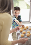 Grandmother offering cupcakes to grandson