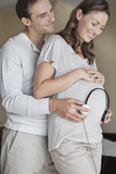 Man holding headphones to pregnant wife?s stomach