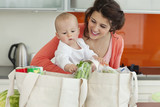 Mother holding baby and unloading groceries