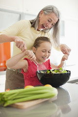 Grandmother and granddaughter preparing salad together