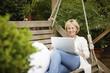 Woman sitting on swing using laptop