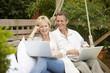 Couple sitting in swing using laptops