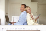 Couple in bedroom using laptop and digital tablet