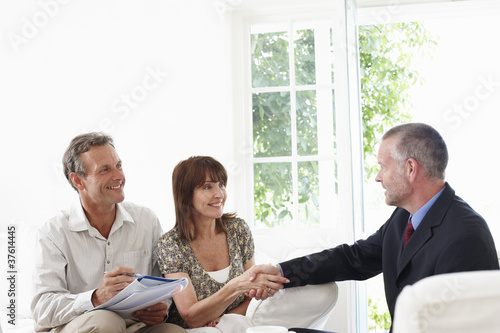 Couple shaking hands with financial advisor