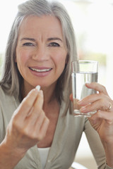 Woman holding glass of water and taking pill