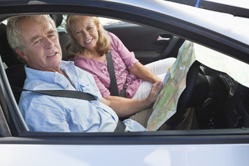 Couple looking in map in car