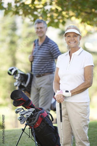 Couple standing with golf clubs and bag