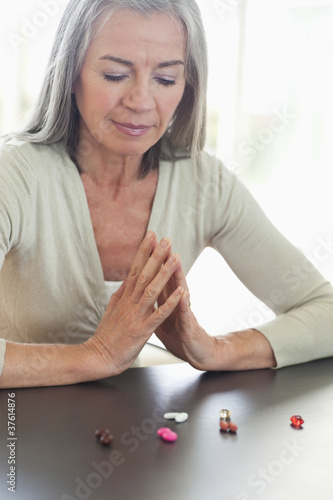 Woman looking at pills on counter