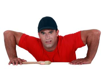Muscular man lifting himself up onto a ledge