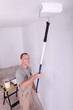 Decorator using a roller extension to paint a ceiling white