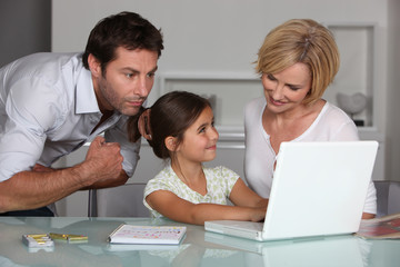 Parents and daughter with laptop computer