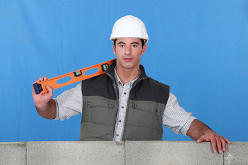 Man stood by wall with spirit-level