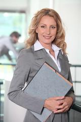 Blonde businesswoman holding files