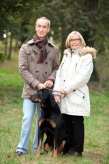 mature couple walking in a park with their dog