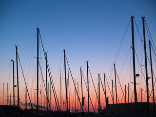 Masts of sail boats in sunset