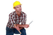 A dreamy tradesman holding a hammer and chisel