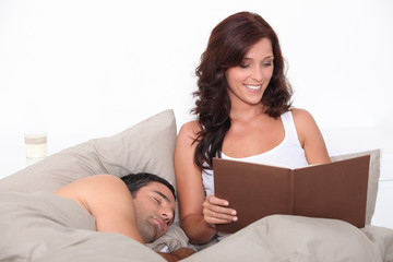 Woman reading in bed as her partner sleeps