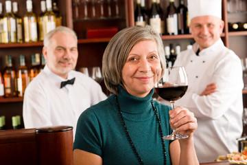 Restaurant manager taste glass red wine bar