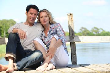 mid age couple seated on a pontoon near a lake