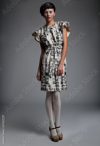 Fashion model in retro dress standing in studio