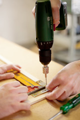 drilling a hole in the wood with an electric drill