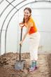 female gardener spading  in greenhouse