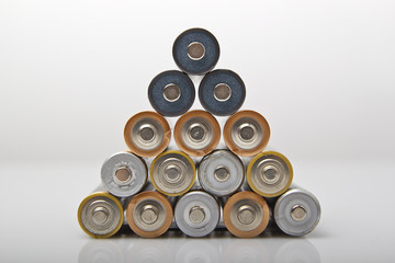used and new various AA batteries stacked in pyramid shape
