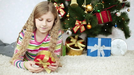 Girl with a gift lying on the floor