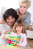 Parents building blocks with their daughter