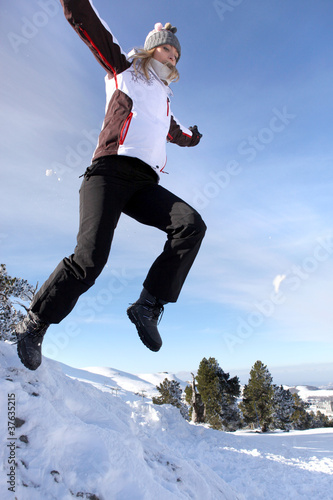 Woman jumping onto a pile of snow