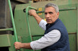 Farmer climbing into a tractor