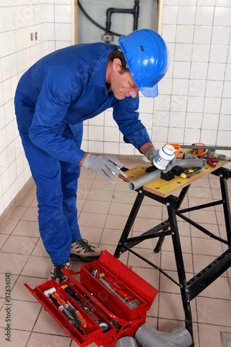 experienced plumber at work with miscellaneous tools