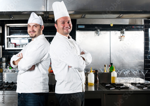 Portrait of two chefs smiling and holding kitchen utensil