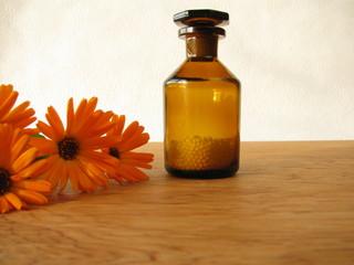 Homöopathische Globuli in der Medizinflasche und Ringelblumen