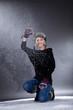 Junge hübsche Frau wirft mit Schnee und lacht